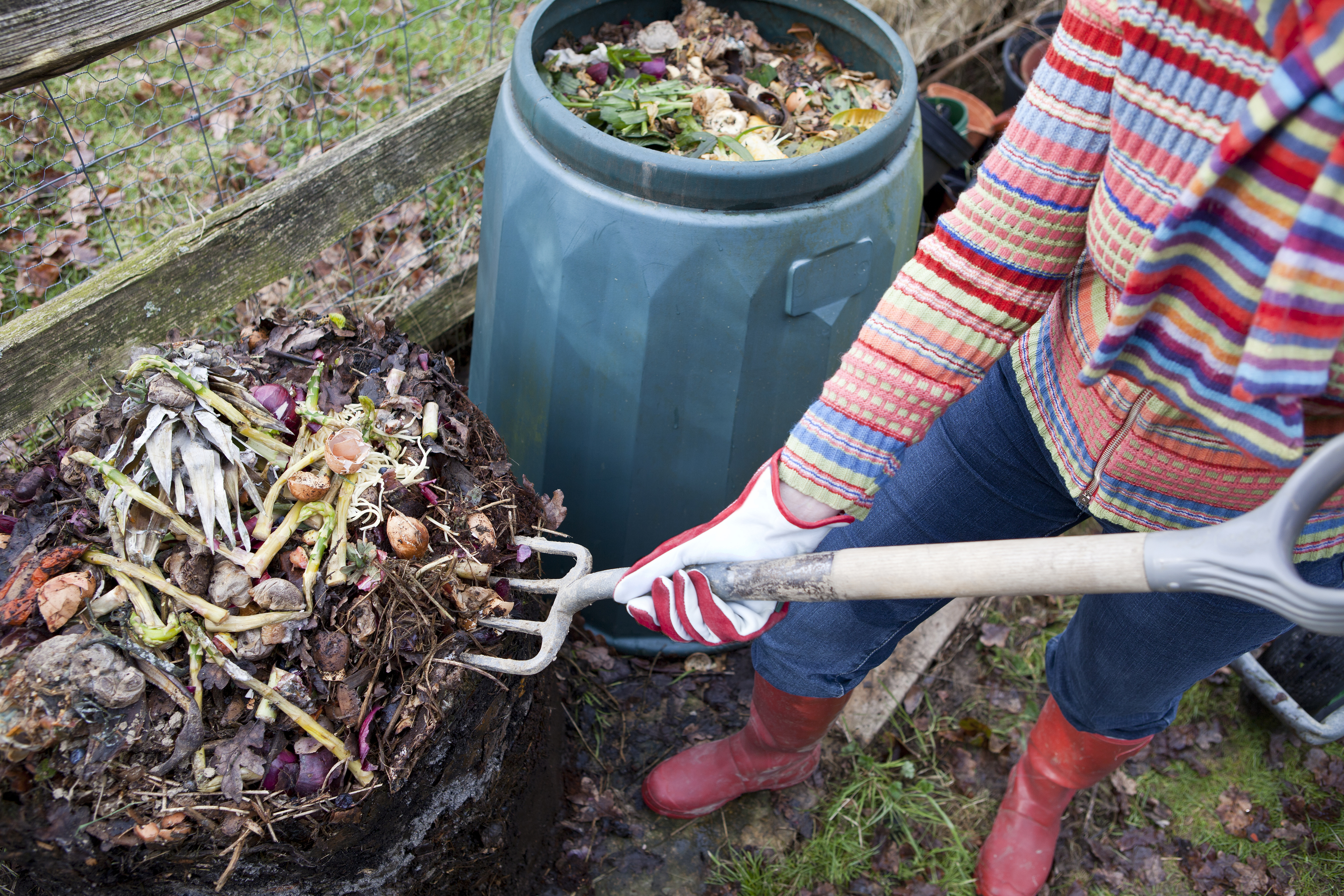 Woman moving composting materials with pitchfork