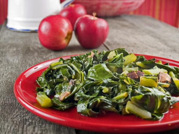 Collard greens and bacon on a red plate with apples and a water pitcher in the background.
