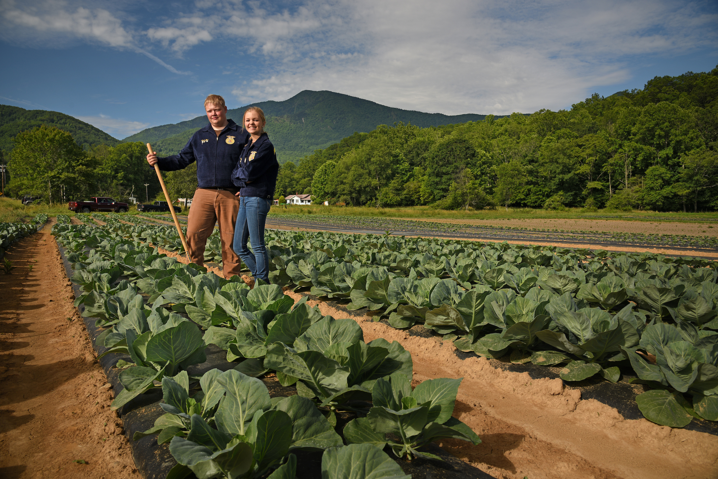 2 people standing in field with collards